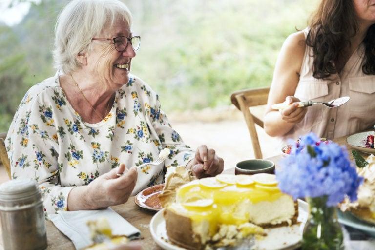 Ältere Frau sitzt mit junger Frau am Tisch - Meminto Stories Muttertag Edition