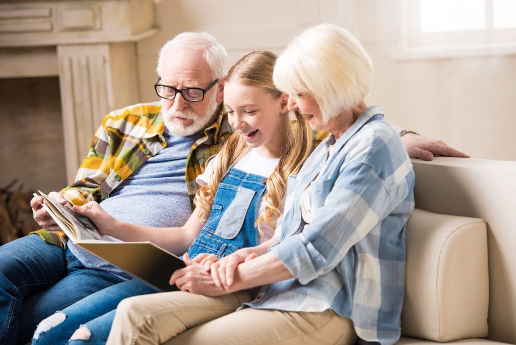 Oma, Opa und Enkelin betrachten die Familiengeschichte